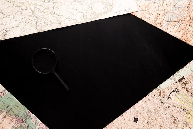Kaarten en loep op zwart bureau Gratis Foto