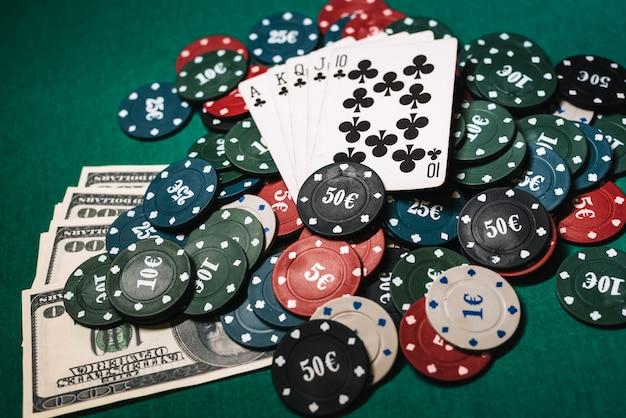 Kaarten met een royal flush op een stapel chips en gelddollars in een pokerspel Premium Foto