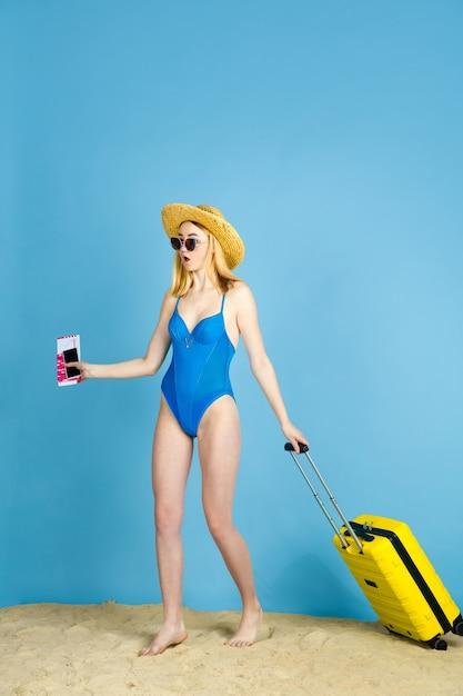 Kaartjes vasthouden. gelukkige jonge vrouw met zak die op reis op blauwe studioachtergrond wordt voorbereid. concept van menselijke emoties, gezichtsuitdrukking, zomervakantie, weekend. zomer, zee, oceaan, alcohol. Gratis Foto