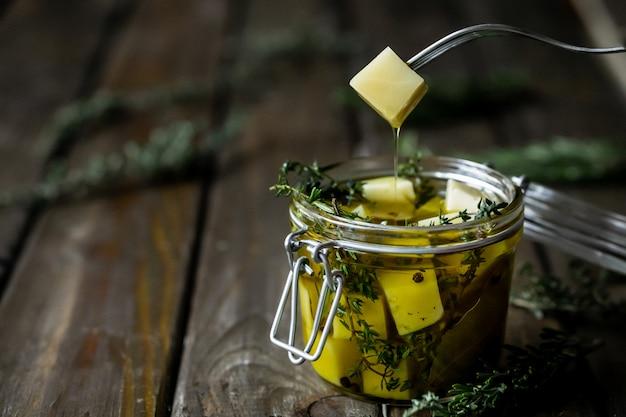 Kaas in olijfolie met aromatische kruiden (tijm en rozemarijn). Premium Foto