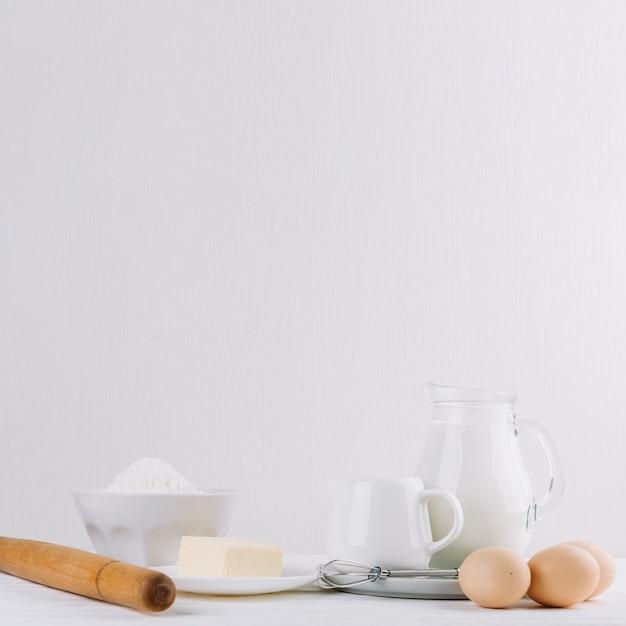 Kaas; meel; melk; deegroller; whisker en eieren op witte achtergrond voor het maken van taart Gratis Foto