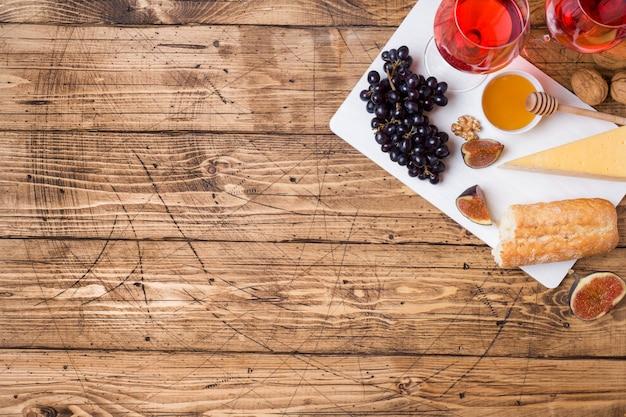 Kaas, wijn, baguette druiven vijgen honing en snacks op de rustieke houten tafelblad met kopie ruimte. Premium Foto