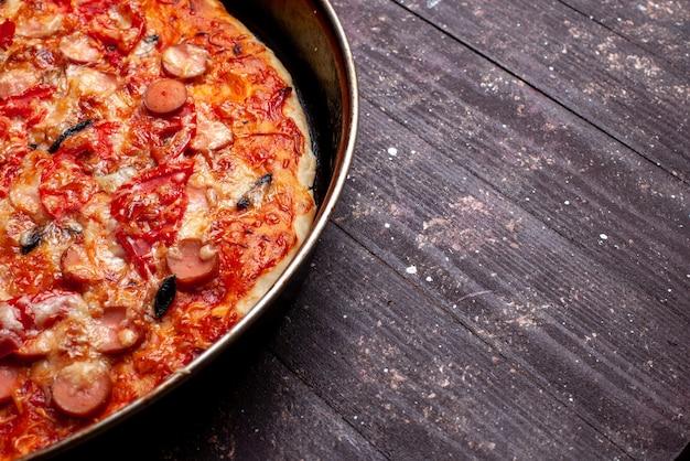 Kaasachtige tomatenpizza met olijven en worstjes in pan op bruin bureau, de kaasworst van het pizzamaaltijd snel voedsel Gratis Foto