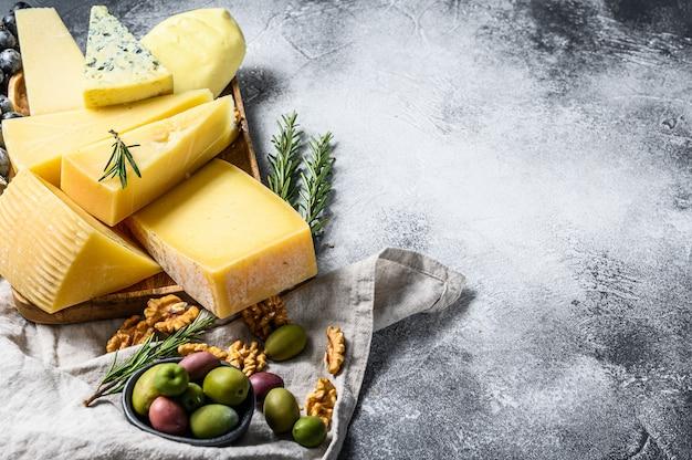 Kaasbord geserveerd met druiven, crackers, olijven en noten. diverse heerlijke snacks. bovenaanzicht copyspace-achtergrond Premium Foto