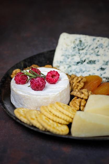 Kaasplaat op donker met camembertkaas, blauwe kaas, gauda en bessen en snacks Gratis Foto