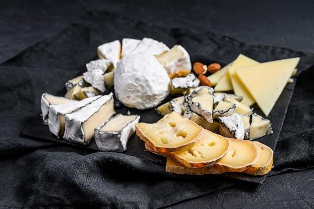 Kaasplateau geserveerd met noten en vijgen. frans voorgerecht. zwarte achtergrond. bovenaanzicht Premium Foto