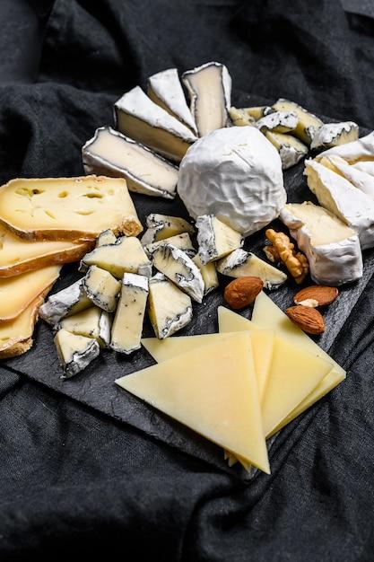 Kaasplateau geserveerd met noten en vijgen. zwarte achtergrond. bovenaanzicht Premium Foto