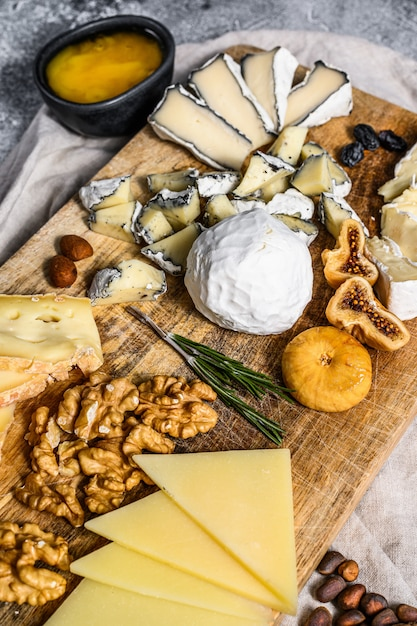 Kaasschotel met franse biologische kazen, vijgen, noten op grijze achtergrond. bovenaanzicht lekkere kaas voorgerecht Premium Foto