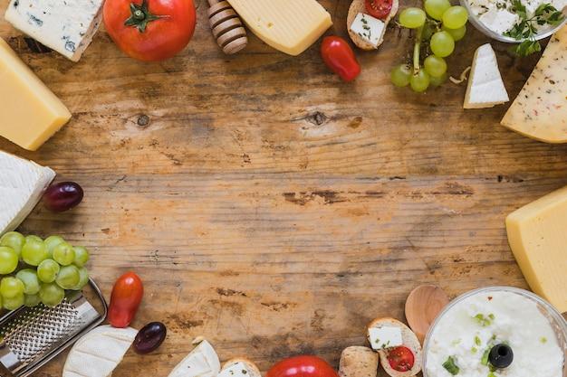 Kaasschotel met tomaten, druiven en minisandwiches op houten bureau met ruimte voor het schrijven van de tekst Gratis Foto