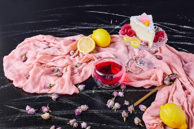 Kaastaart met fruit en thee op roze doek. Gratis Foto