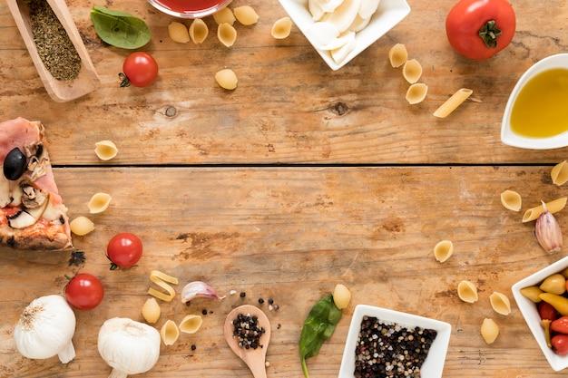 Kader met italiaanse pizza en ingrediënten over houten bureau wordt gemaakt dat Gratis Foto