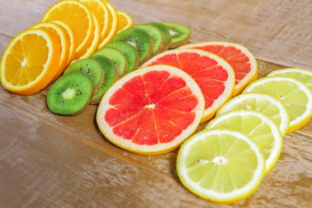 Kader met plak van sinaasappelen, citroenen, kiwi, grapefruitpatroon op houten achtergrond. Premium Foto