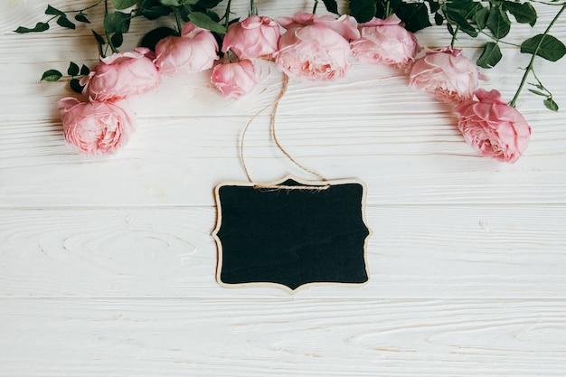 Kader van roze roze bloemen op witte houten achtergrond wordt gemaakt die. Premium Foto