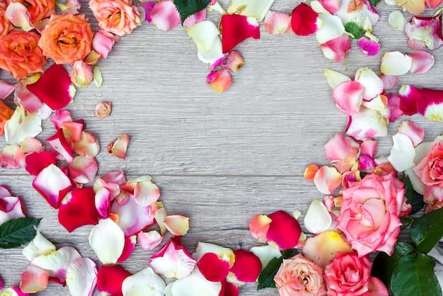 Kaderhart van roze bloemen op houten achtergrond voor valentijnskaartendag die wordt gemaakt. Premium Foto