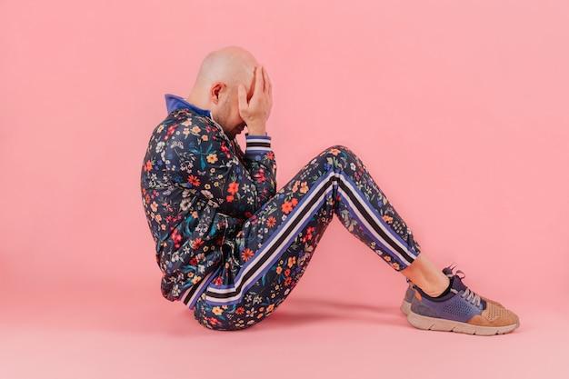 Kale man in modieuze kleding zitten met handen op zijn gace over roze achtergrond. Premium Foto