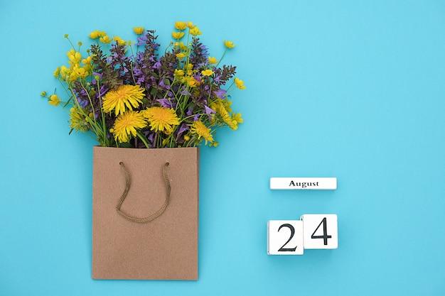 Kalender 24 augustus en veld kleurrijke rustieke bloemen in ambachtelijke pakket op blauwe achtergrond. wenskaart plat leggen Premium Foto