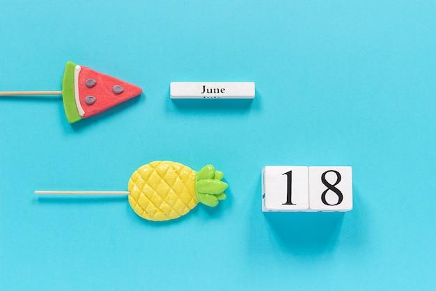 Kalenderdatum 18 juni en zomerfruit snoep ananas, watermeloen-lollies. Premium Foto