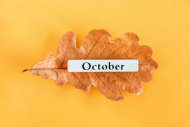 Kalendermaand oktober op herfst eiken blad op geel. Premium Foto