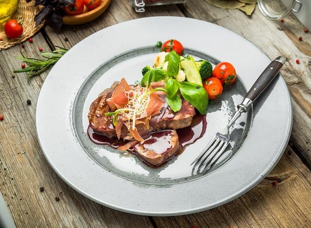 Kalfsmedaillons, met saus op een bord. houten achtergrond Premium Foto