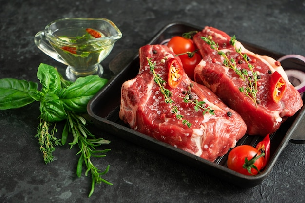 Kalfsvlees bot keu bal op grillpan met kruiden, kruiden en olijfolie op donkere achtergrond. selectieve aandacht Premium Foto