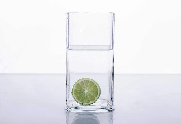 Kalk spatten in glas water op witte achtergrond Premium Foto