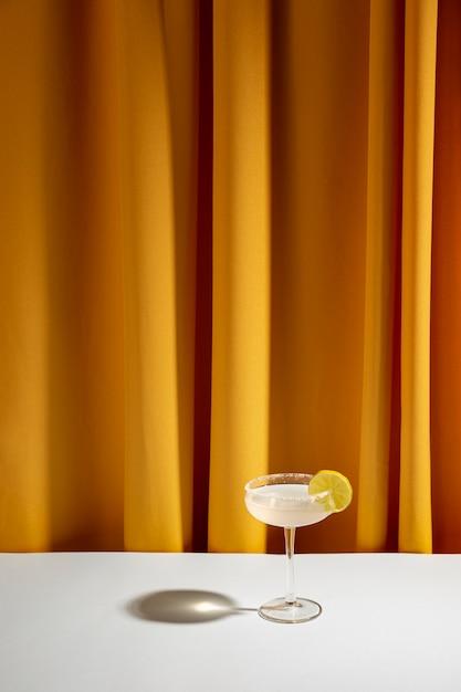 Kalkcocktail in schotelglas op witte lijst tegen geel gordijn Gratis Foto