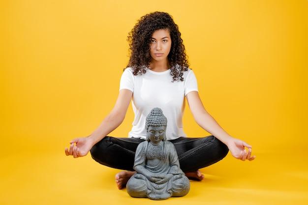 Kalm jong zwarte die en yoga met boedha mediteren doen die over geel wordt geïsoleerd Premium Foto