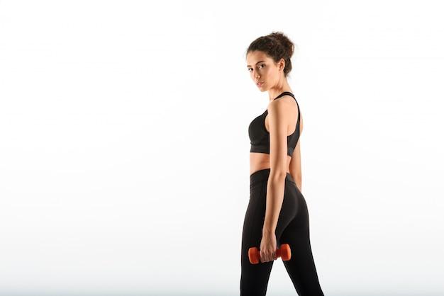 Kalm krullend brunette fitness vrouw met halters Gratis Foto