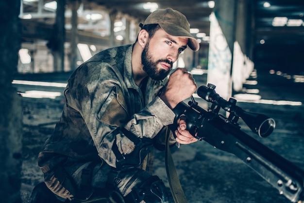 Kalme en vredige soldaat kijkt recht vooruit. hij wacht. jonge man zit op een knie. man draagt een militair uniform. Premium Foto