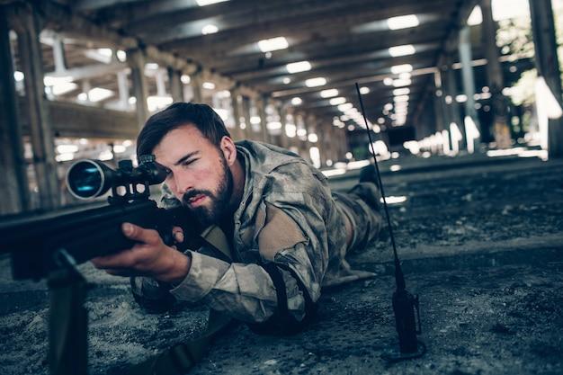 Kalme en vreedzame jonge man ligt op de grond en neemt doel. hij ziet er heel serieus uit. guy gebruikt daarvoor een geweer. ook kijkt hij door de lens. guy wacht op. Premium Foto