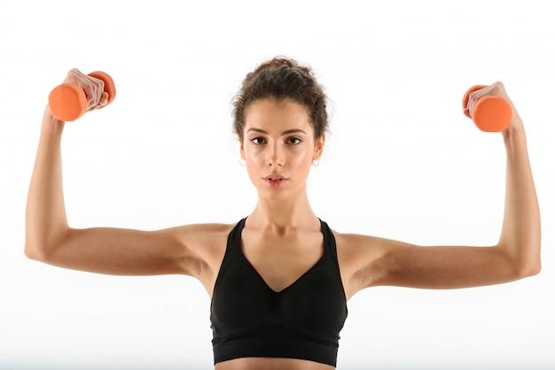 Kalme krullende donkerbruine geschiktheidsvrouw die oefening met domoren doen en haar bicepsen tonen Gratis Foto