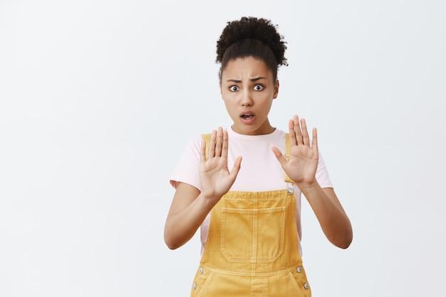Kalmeren, pistool neerleggen. intens bezorgde en nerveuze bange afro-amerikaanse vrouw met krullend haar in gele overall, handpalmen omhoog, vragen om te ontspannen en te chillen, troost proberen depressieve vriend Gratis Foto