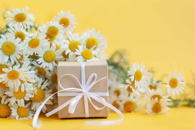 Kamille bloemen en cadeau of huidige doos op geel Premium Foto