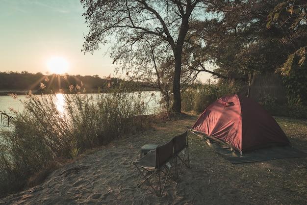 Kamperen met tent, stoelen en kampeerspullen. zonsopgang over okavango-rivier, de grens van namibië botswana. avontuurlijk reizen en outdoor-activiteiten in afrika. gestemd beeld, vintage stijl. Premium Foto