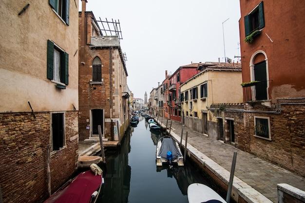 Kanaal met gondels in venetië, italië. architectuur en bezienswaardigheden van venetië. ansichtkaart van venetië met gondels van venetië. Gratis Foto