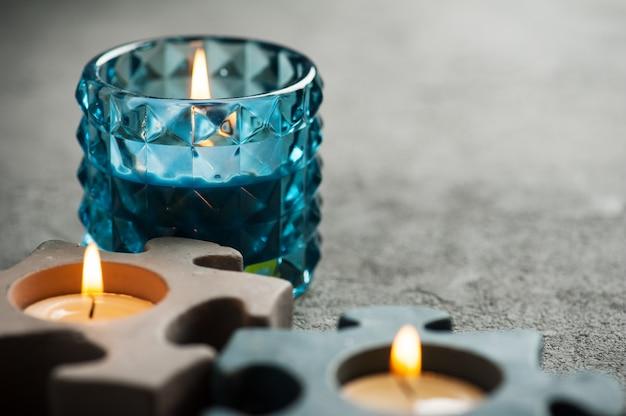Kandelaars met brandende kaarsen op steenachtergrond Premium Foto