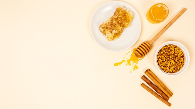 Kaneelstok; honingraat; pot met honing en bijen stuifmeel met kopie ruimte achtergrond Gratis Foto
