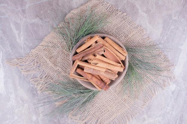 Kaneelstokjes in een houten beker met eiken takken rond. Gratis Foto