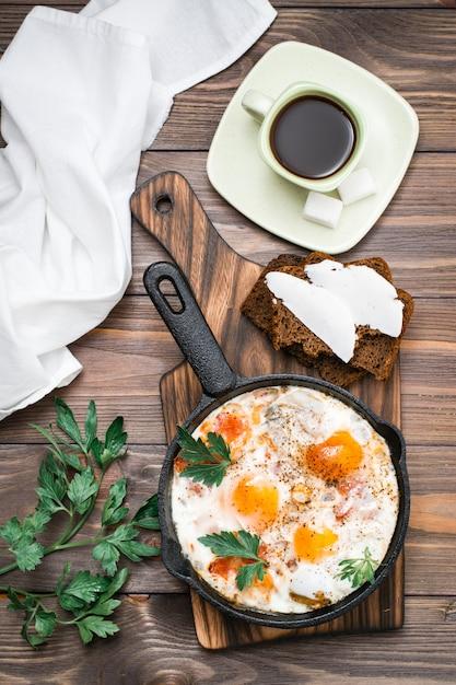 Kant-en-klaar ontbijt: shakshuka van gebakken eieren met tomaten en peterselie in een pan, brood met boter en koffie op een houten tafel. bovenaanzicht Premium Foto