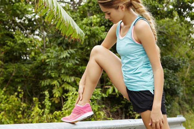 Kant portret van mooie blonde vrouw atleet met lange vlecht in sportkleding ontspannen na de marathon, haar enkel masseren. Gratis Foto