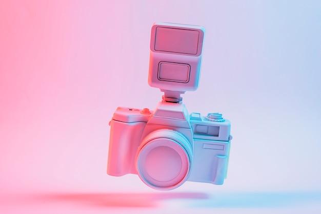Kantel de camera zwevend over de roze achtergrond Gratis Foto