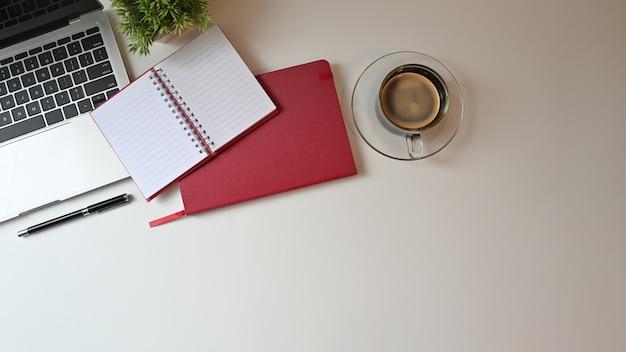 Kantoor bureau bovenaanzicht tafel met laptop, laptop en pen met koffie. Premium Foto