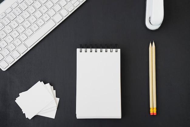 Kantoor bureau met potloden, notitieboekje, kaarten en toetsenbord Gratis Foto