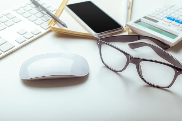 Kantoor bureau tafel met computertoetsenbord, benodigdheden, rekenmachine, pen, glazen Premium Foto