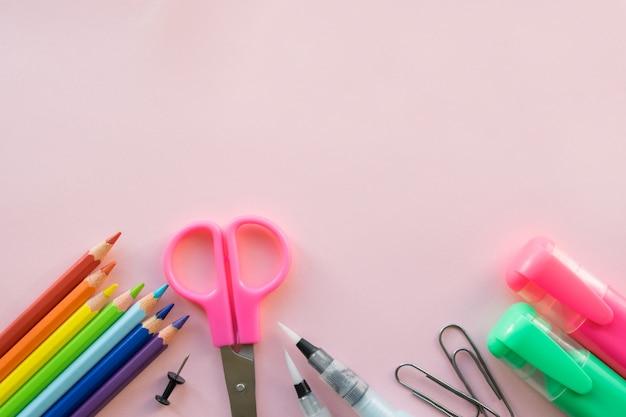 Kantoor- en schoolbenodigdheden op roze achtergrond. copyspace Premium Foto
