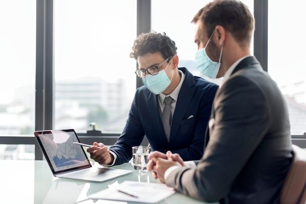 Kantoor in nieuw normaal, mannen met medisch masker covid 19 Gratis Foto