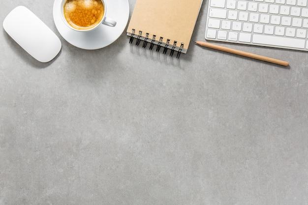 Kantoor tafel met kopje koffie, toetsenbord en kladblok Gratis Foto