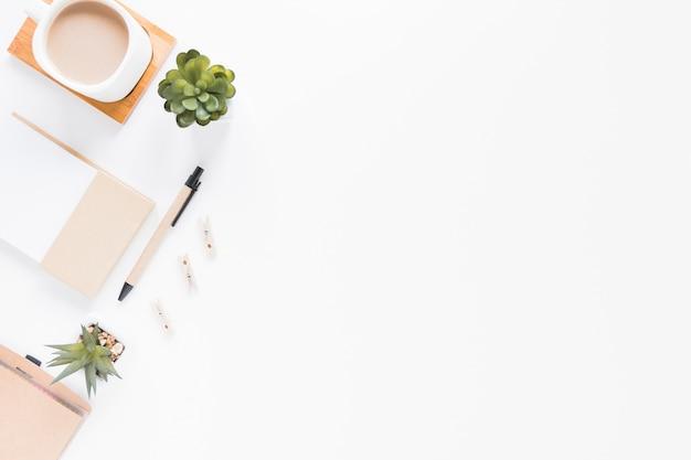 Kantoorbehoeften dichtbij koffiekop en bloempotten op wit bureau Premium Foto