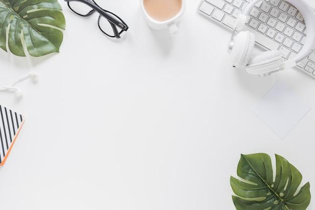 Kantoorbehoeften en apparaten op wit bureau dat met bladeren wordt verfraaid Gratis Foto
