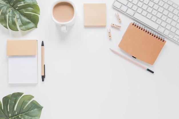 Kantoorbehoeften en toetsenbord op witte lijst met groene bladeren en koffiekop Gratis Foto